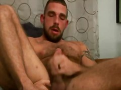 Hairy stud with tattoos jerks off on a futon